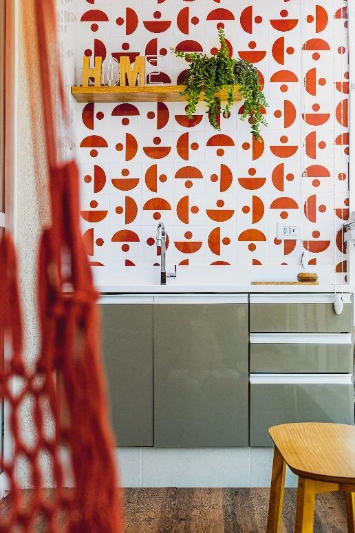 Área gourmet com azulejos geométricos nas cores vermelhas, branca, armário cinza, piso amadeirado e prateleira com acessórios deocrativos.