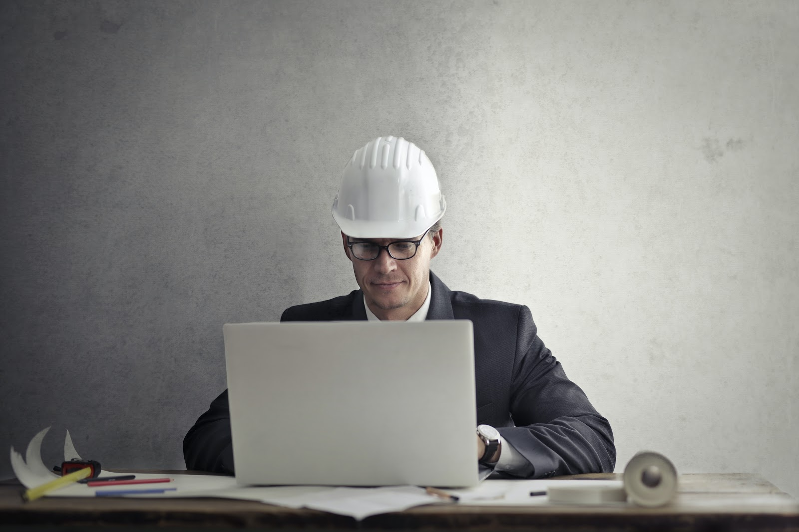 A man in a hard hat uses a laptop on a desk in a gray room