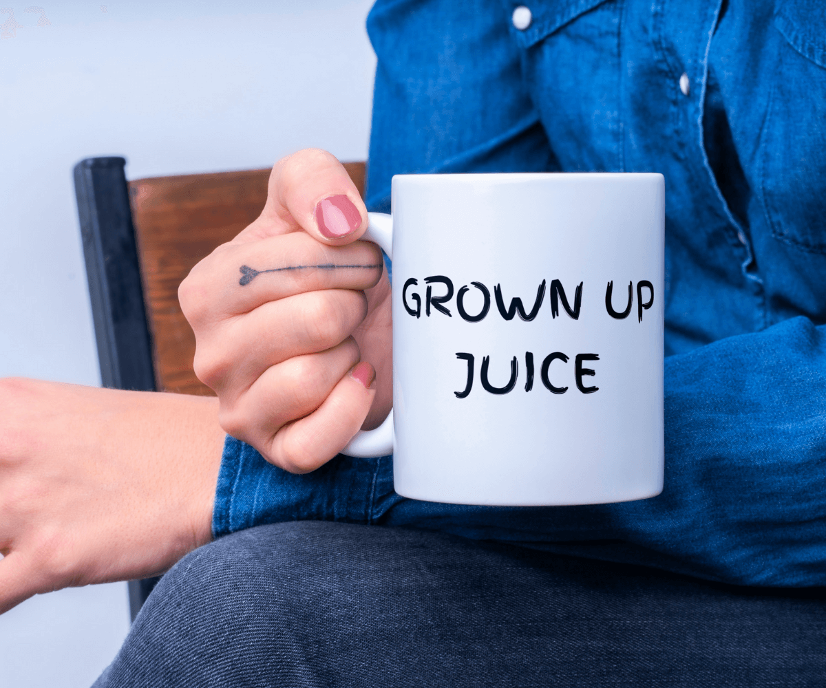 """Female hand holding a white mug with the words """"grown up juice"""" in black font across the front."""