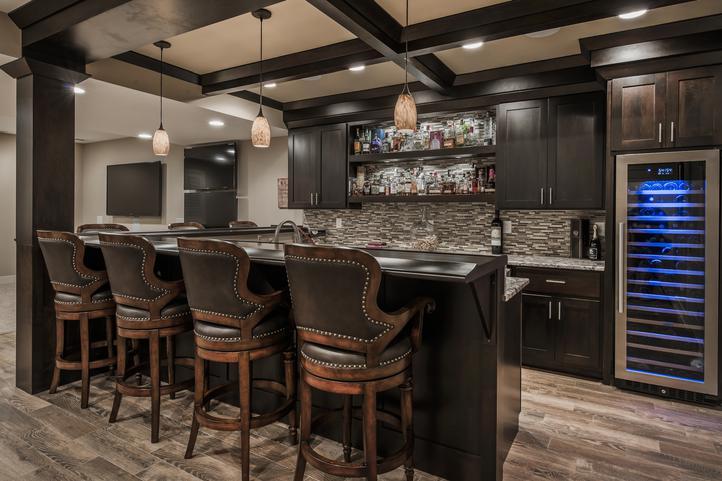 rustic basement wet bar with espresso shaker cabinets, grey stained wood floors, stone backsplash and large wine fridge