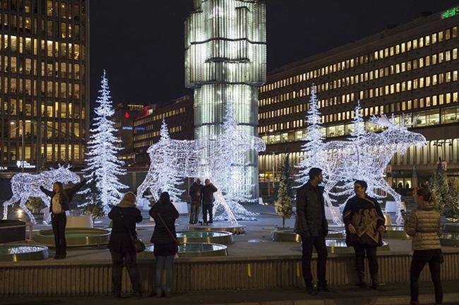 Các bạn trẻ hào hứng chụp ảnh với những tác phẩm trang trí rực sáng ở khu chợ trời bán đồ Giáng sinh ở Stockholm.