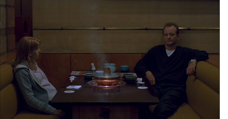 Scarlett Johansson as Charlotte and Bill Murray as Bob in Lost in Translation (2003). Charlotte and Bob are sitting opposite each other at a restaurant booth, a large steaming bowl sits between them. Both are slumped morosely in their seats and don't appear to be talking.