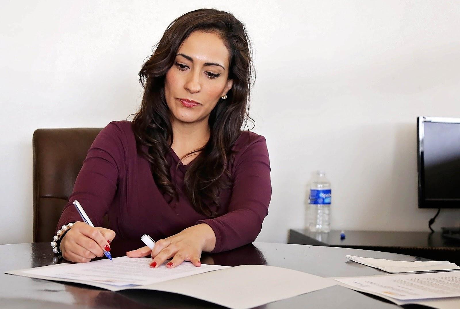 Uma mulher escrevendo em uma pasta.