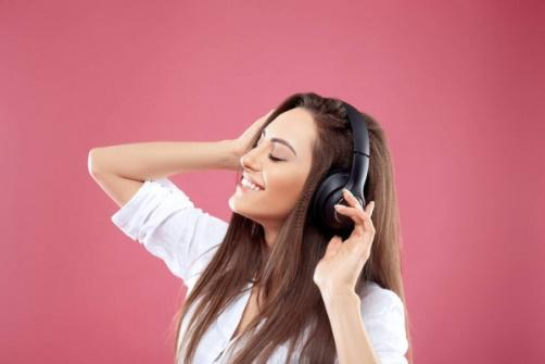 Beautiful woman listening to music using wireless headphones in studio  isolated over pink background.Girl enjoying wireless earphones and dancing.  — accessory, fashion - Stock Photo | #312518512
