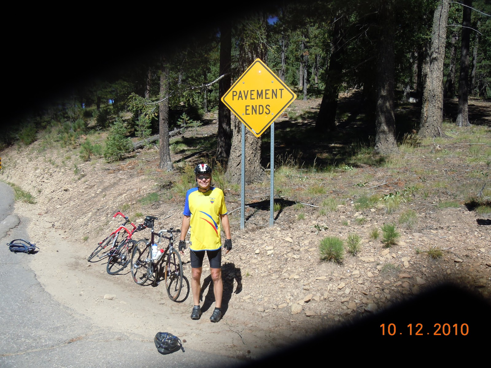 End of Mt. Graham bicycle ride - cyclist, bicycle and road Pavement Ends sign.