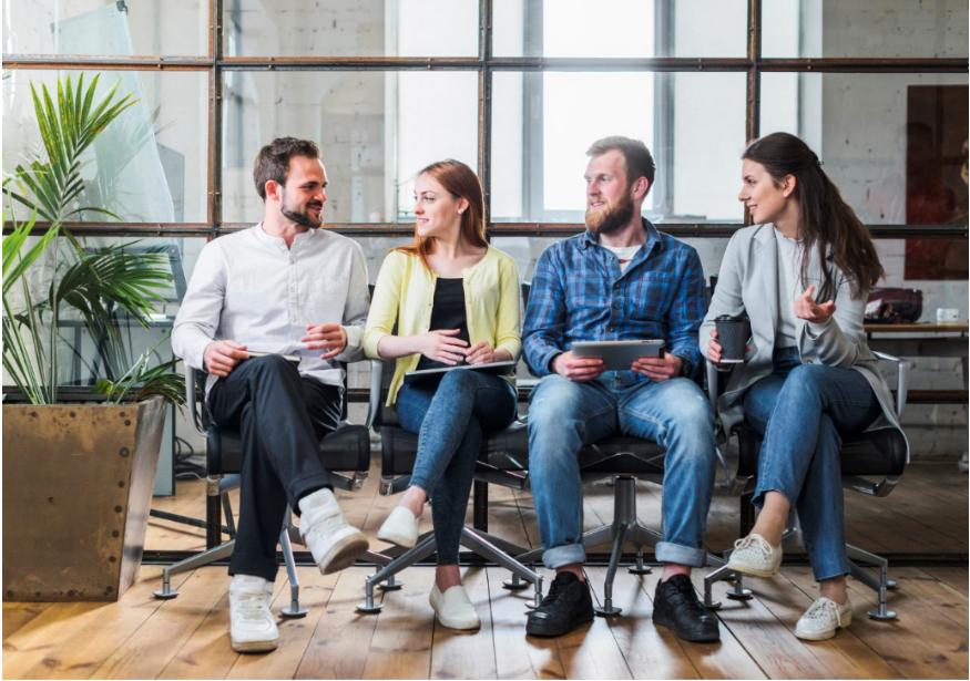 Dois homens e duas mulheres sentados em cadeiras de trabalho conversam