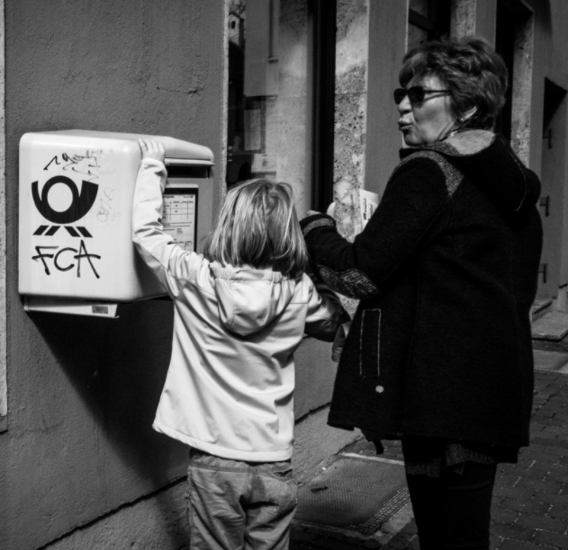 Young child and adult mailing a postcard