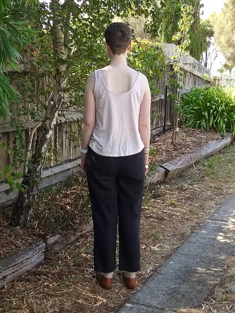 Siobhan stands in front of a tree-lined fence. She wears a pink tank top, black elastic waist straight leg linen pants and brown loafers. Her back is to the camera.