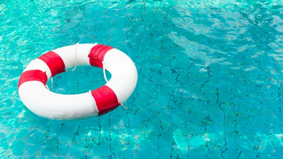 a red-and-white life preserver floating in a sparkling swimming pool