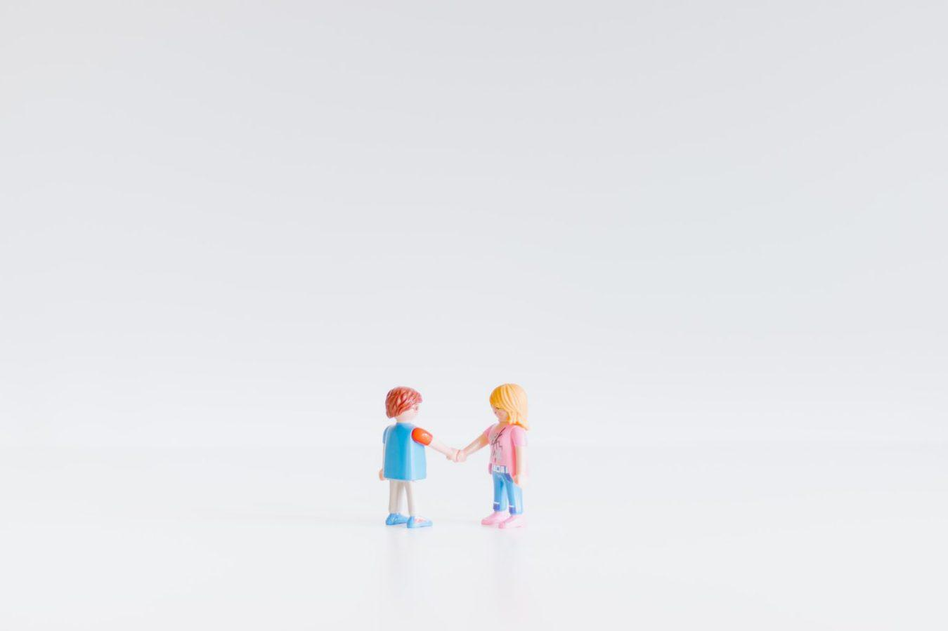 Two toy figurines shaking hands