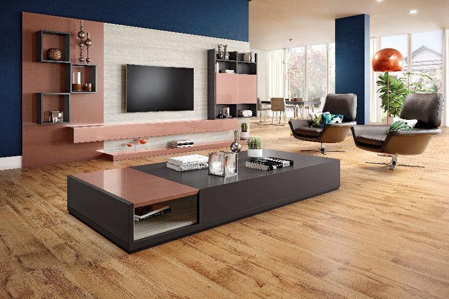 Sala com piso de madeira, mesa de centro grande de madeira cinza e detalhe rose, painel de TV de MDF rose, cinza e tom neutro, poltronas de couro marrom e abajur marrom