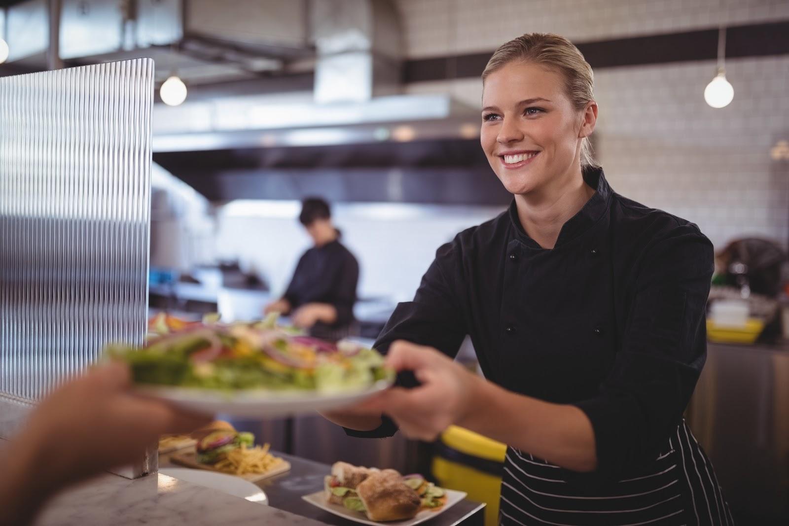 Restaurant worker serving food from kitchen window