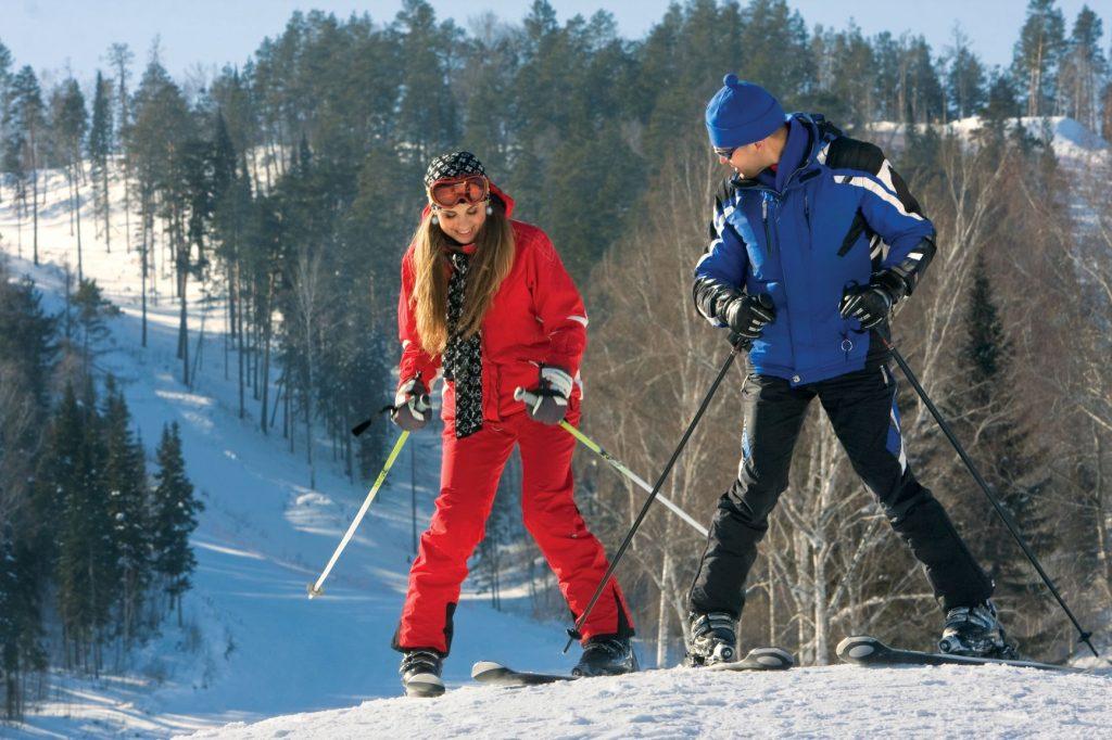 Profesor enseñando a esquiar a la alumna