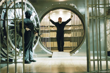 Screen capture from the movie 'Inside Man' featuring a man standing in the open door of a bank vault with another masked and carrying a gun standing nearby