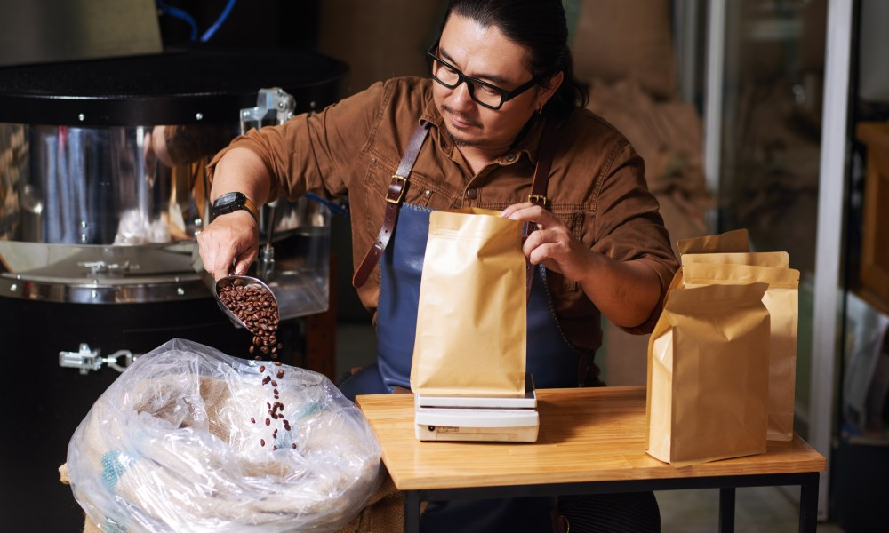 roaster putting roasted beans into a kraft paper coffee bag