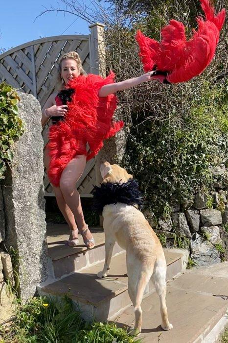 Mujer vestia de bailarina de can can mientras pasea con su perro