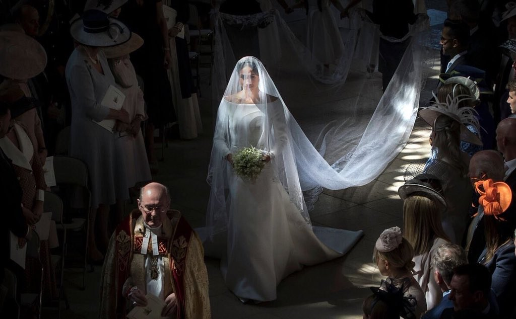 Meghan Markle walks gracefully down the aisle of her royal wedding, looking ethereal.