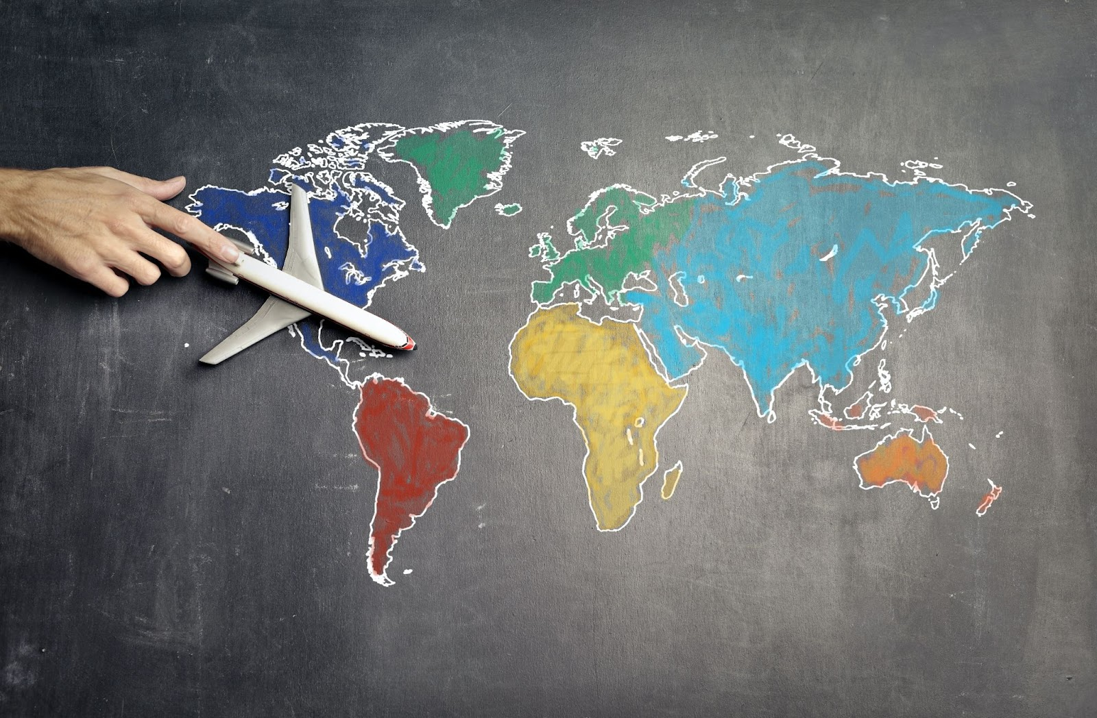 A colored map of the world with a toy plane