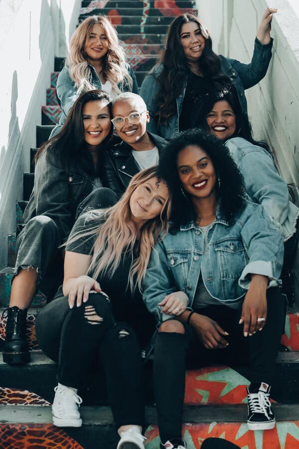 Grupo de amigas sentadas em uma escada e posando para foto
