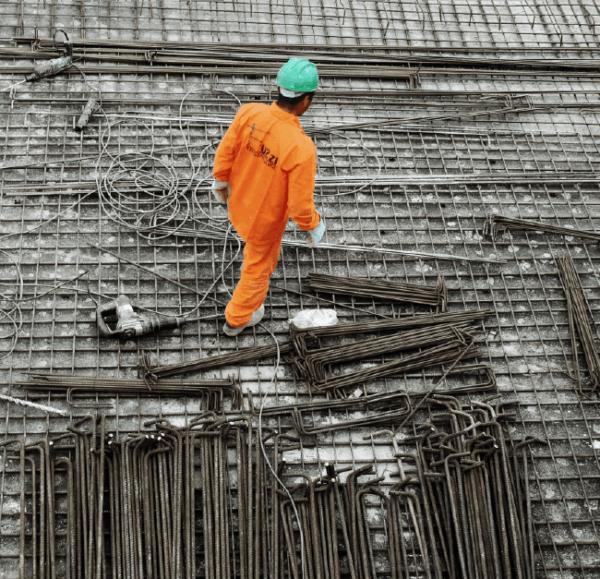 homem em meio às ferragens da construção, usando macacão laranja, capacete verde, luvas e botas