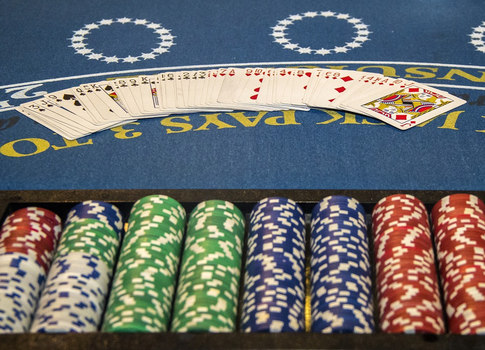 Eight piles of white, red, green, and blue poker chips are lined up in front of a deck of cards spread across a blue betting table