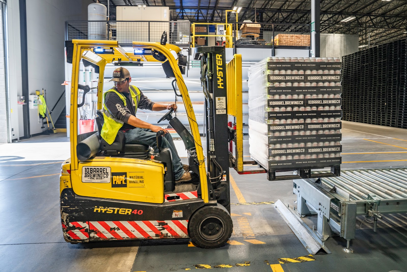 A man drives a forklift in a warehouse