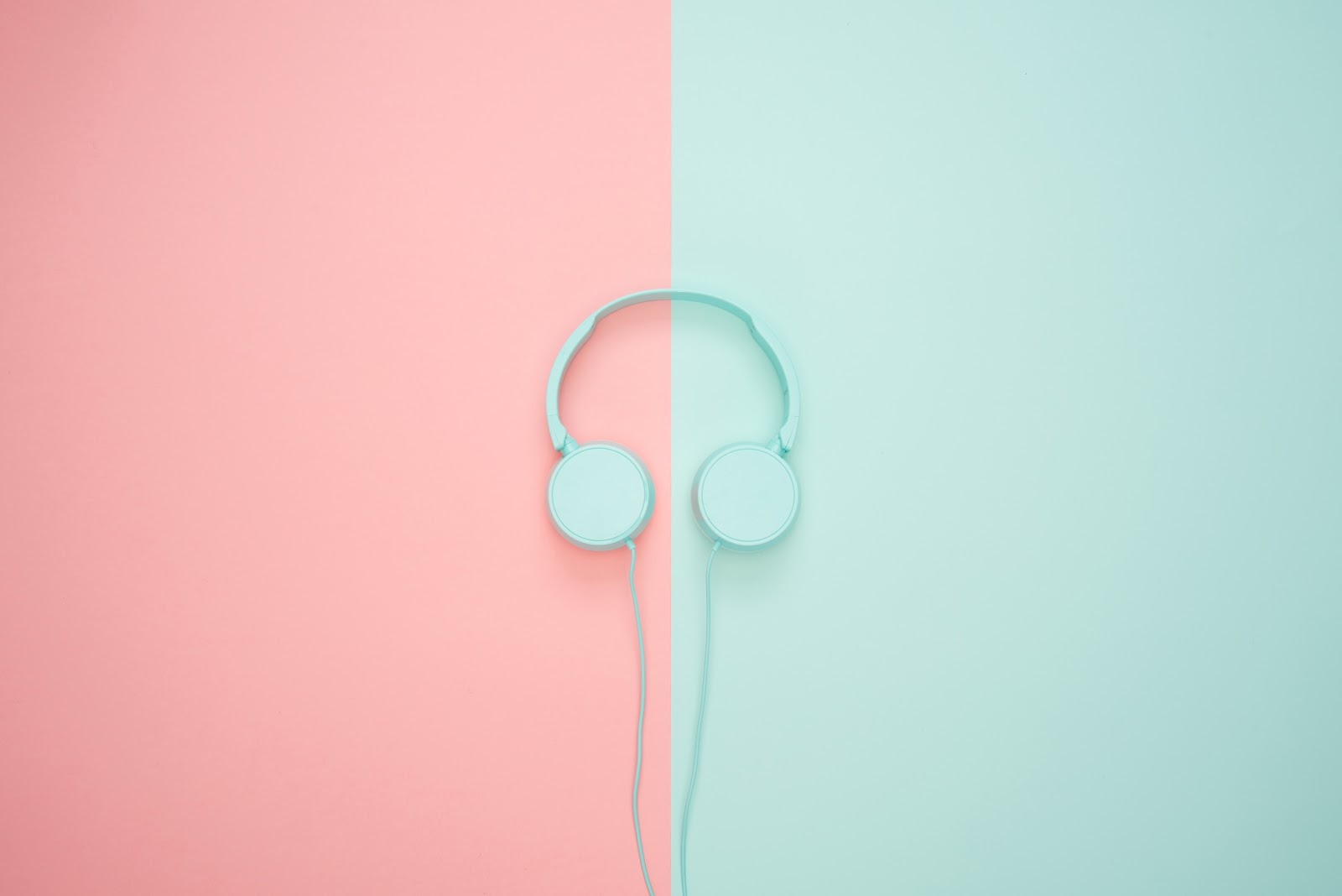 white-headphone-on green and pink background podcasts equipment