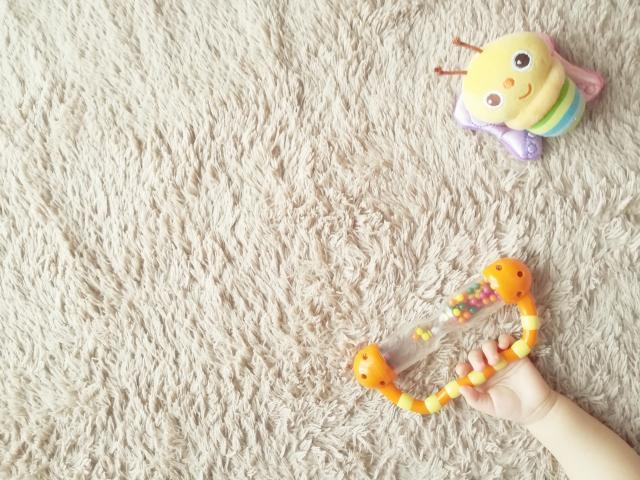 おもちゃやがらがらで遊ぶ赤ちゃんの手