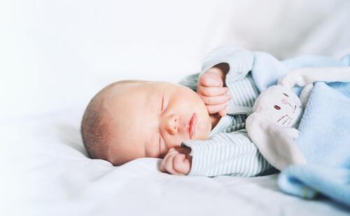 ベビー布団の上で眠っている産まれたばかりの赤ちゃん