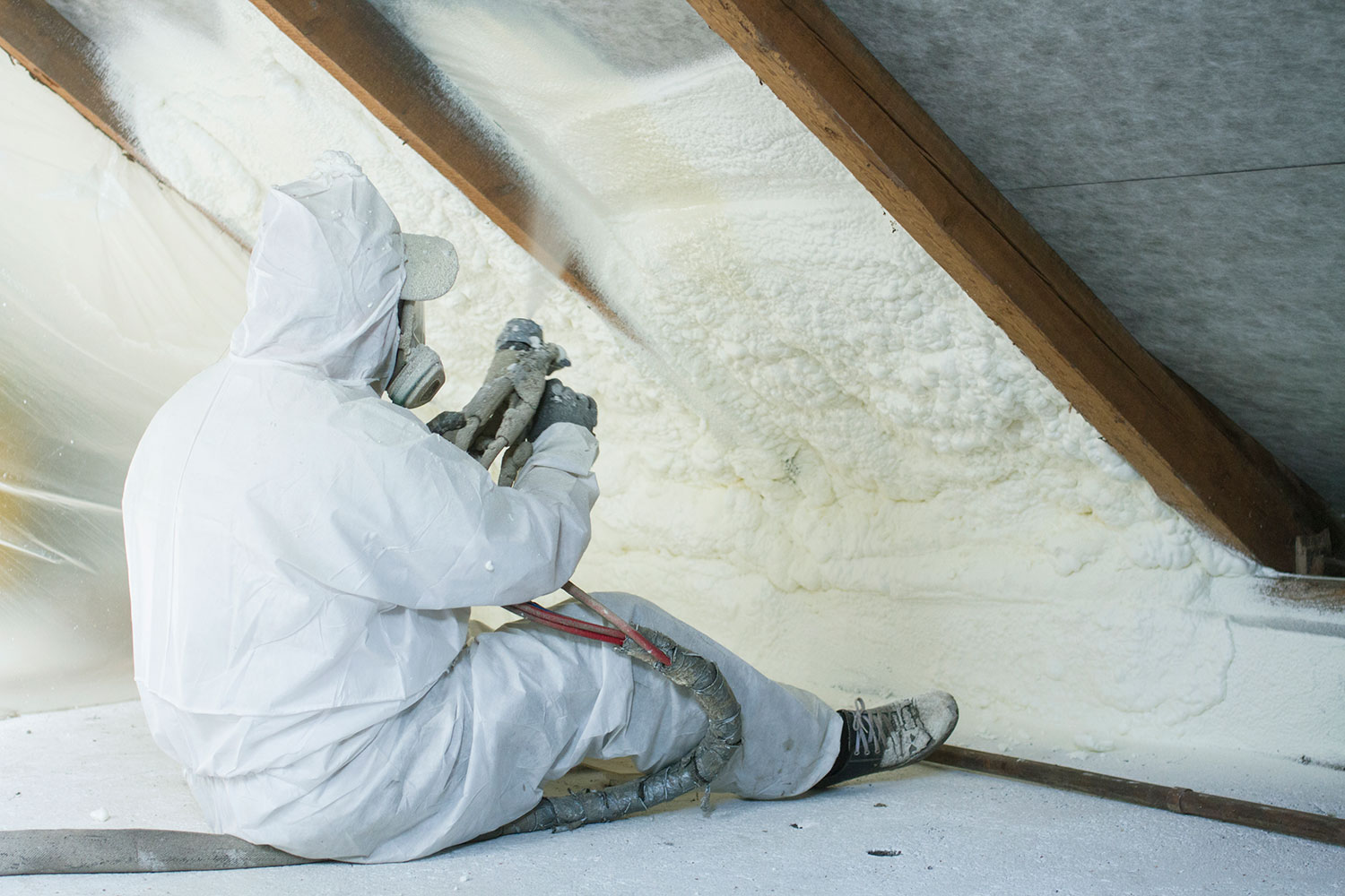 Techinician applying low cost spray foam insulation