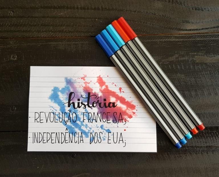 Fotografia com canetas e um esquema colorido com o título história.