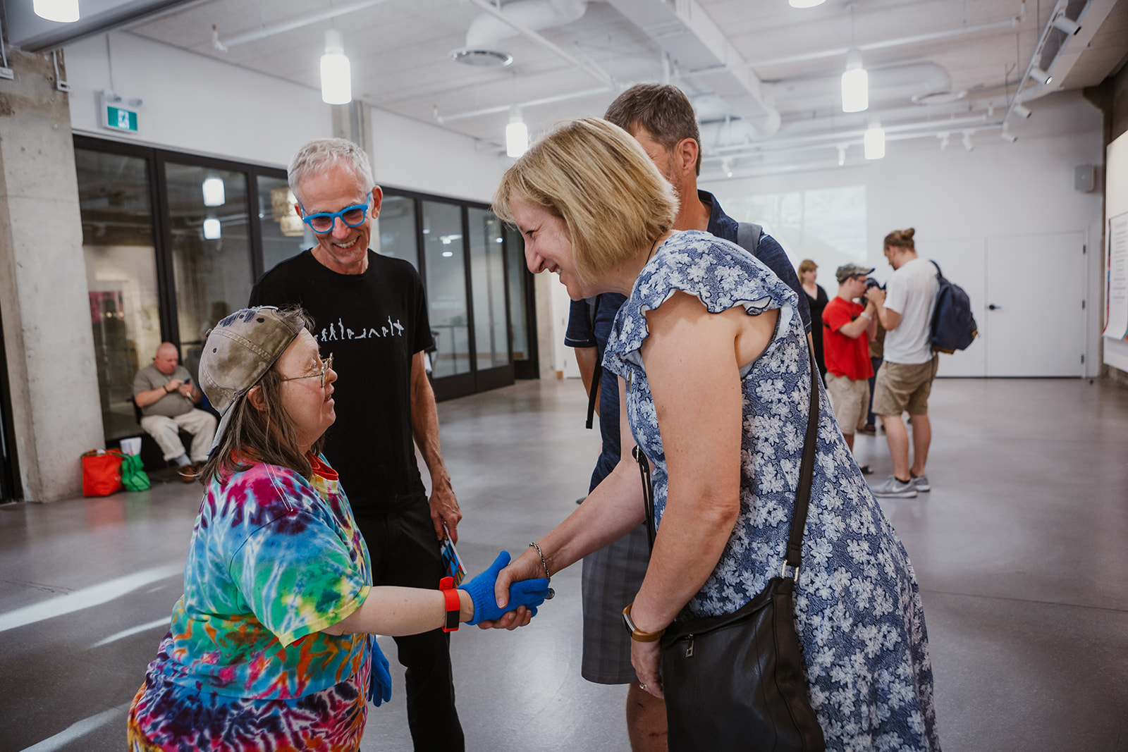 Teresa smiles as a friend from the disability support community shakes her hand. Photo: This Is It Studios.