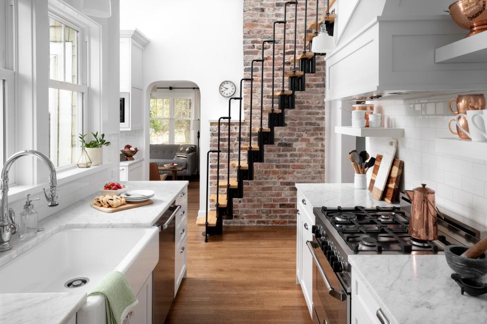 small white galley kitchen in a downtown loft. a kitchen work triangle is created with large white farmhouse sink, stainless steel stove and dishwasher.