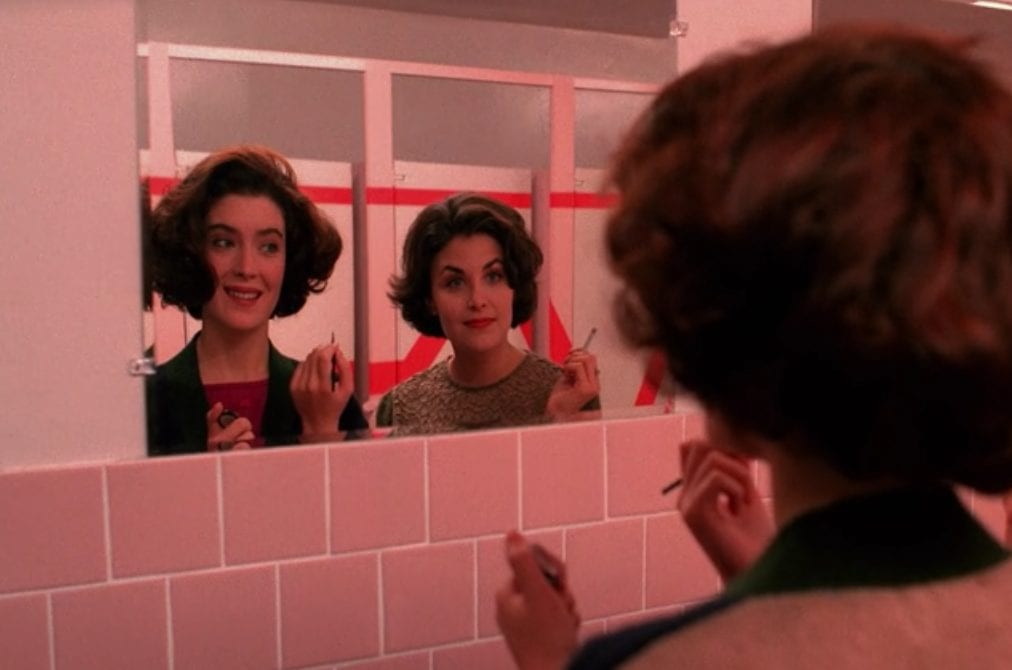 donna and audrey reflected in the school restroom mirror putting on makeup and smoking