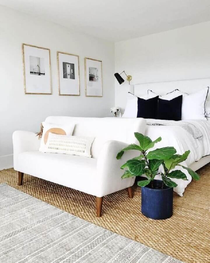 Quarto de casal com decoração toda branca, paredes, teto e sofá branco e tapete de palha.