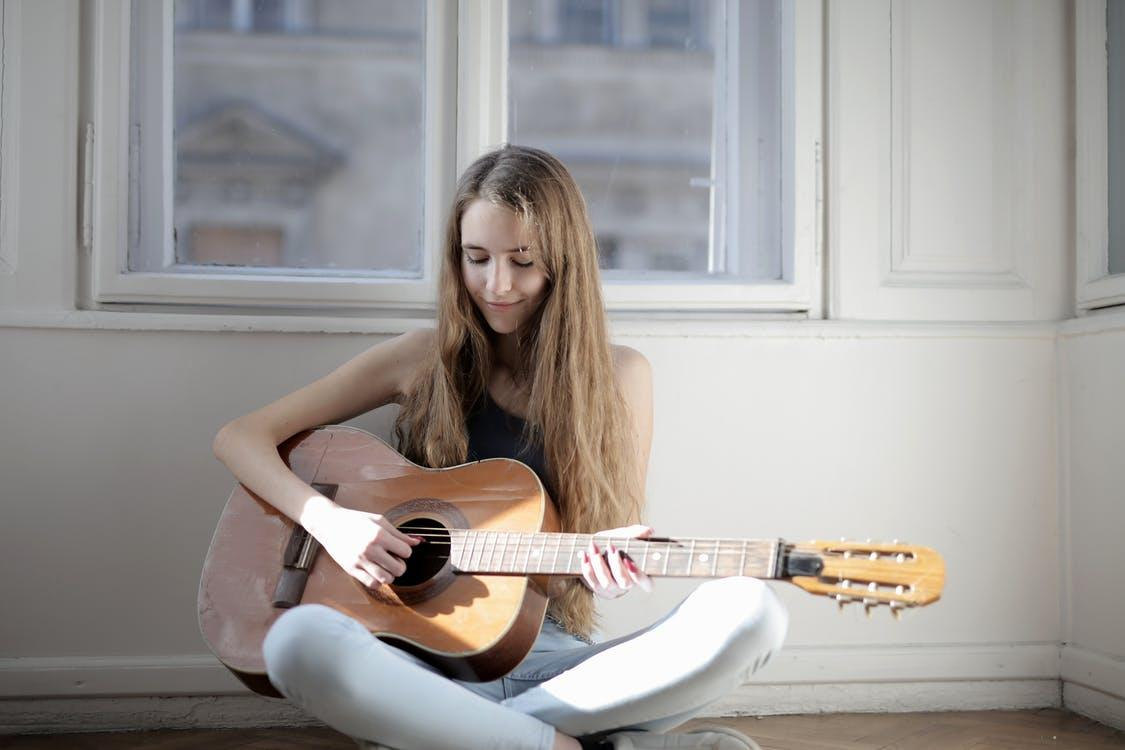 Woman Playing Brown Acoustic Guitar