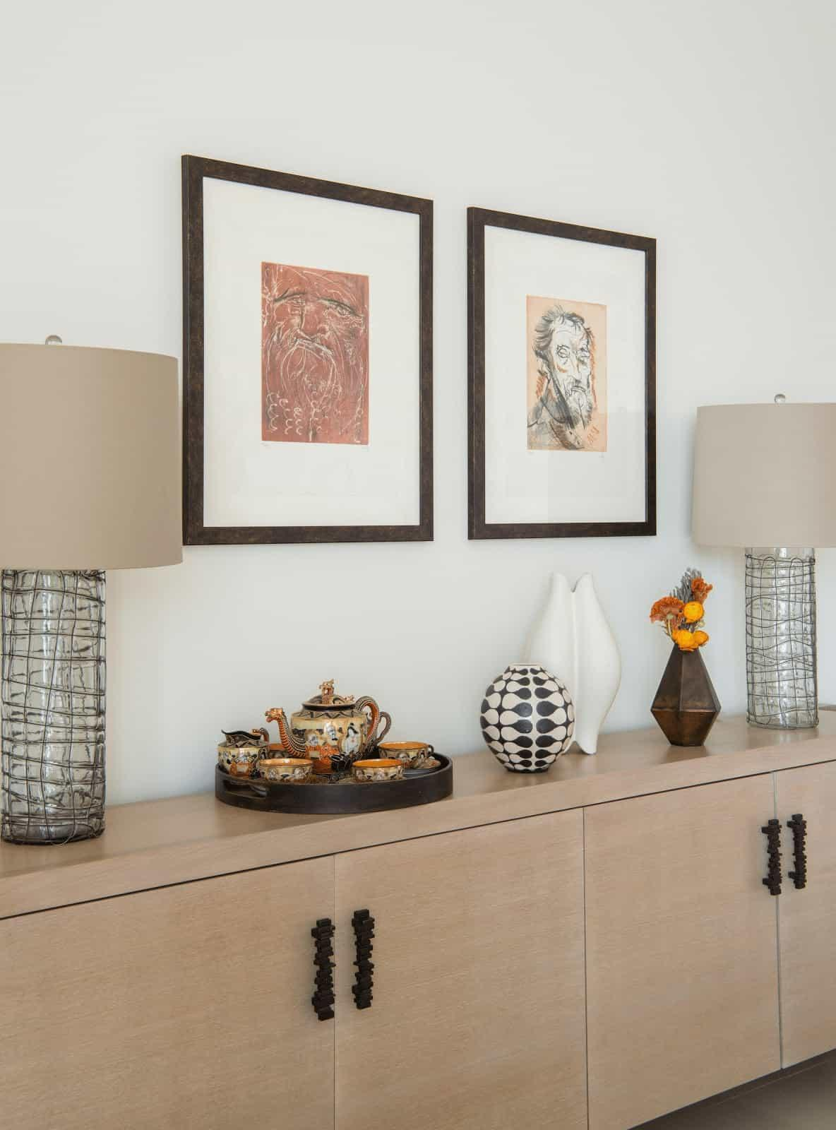 """A large console table with glass lamps and the homeowner""""s art pieces."""