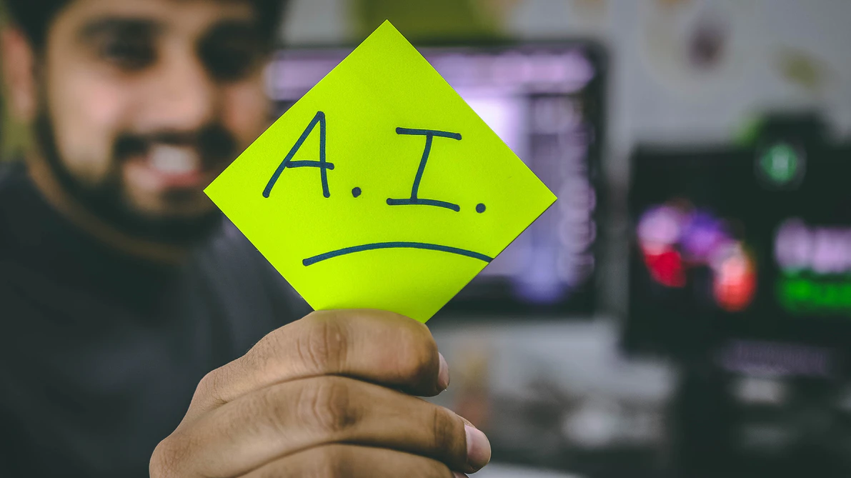 Man holding up post-it note with 'A.I.' written on it