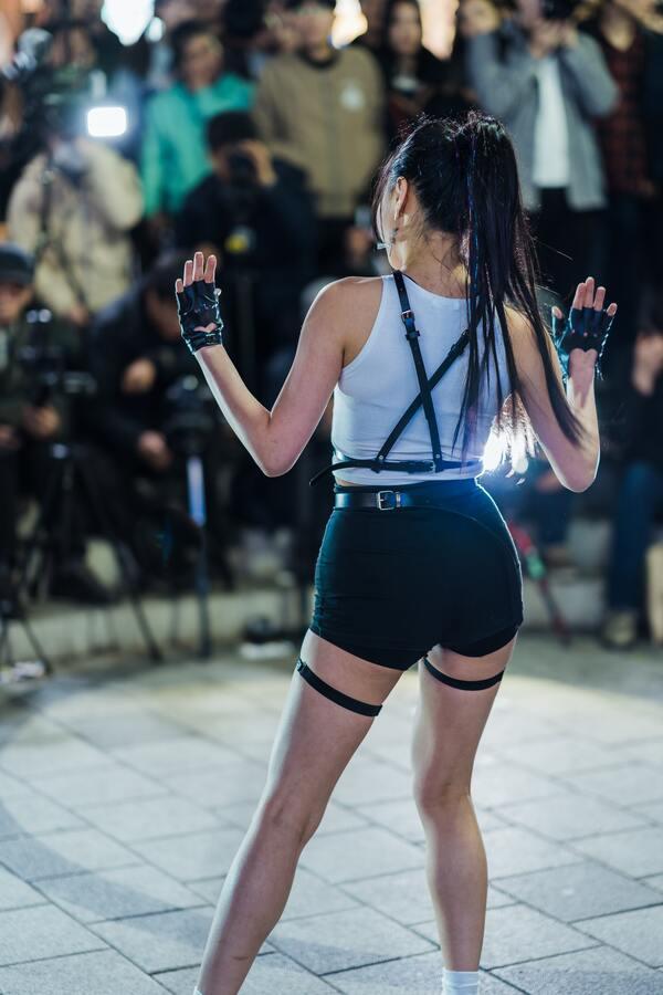 Foto de uma artista k-pop sendo fotografada por paparazzi