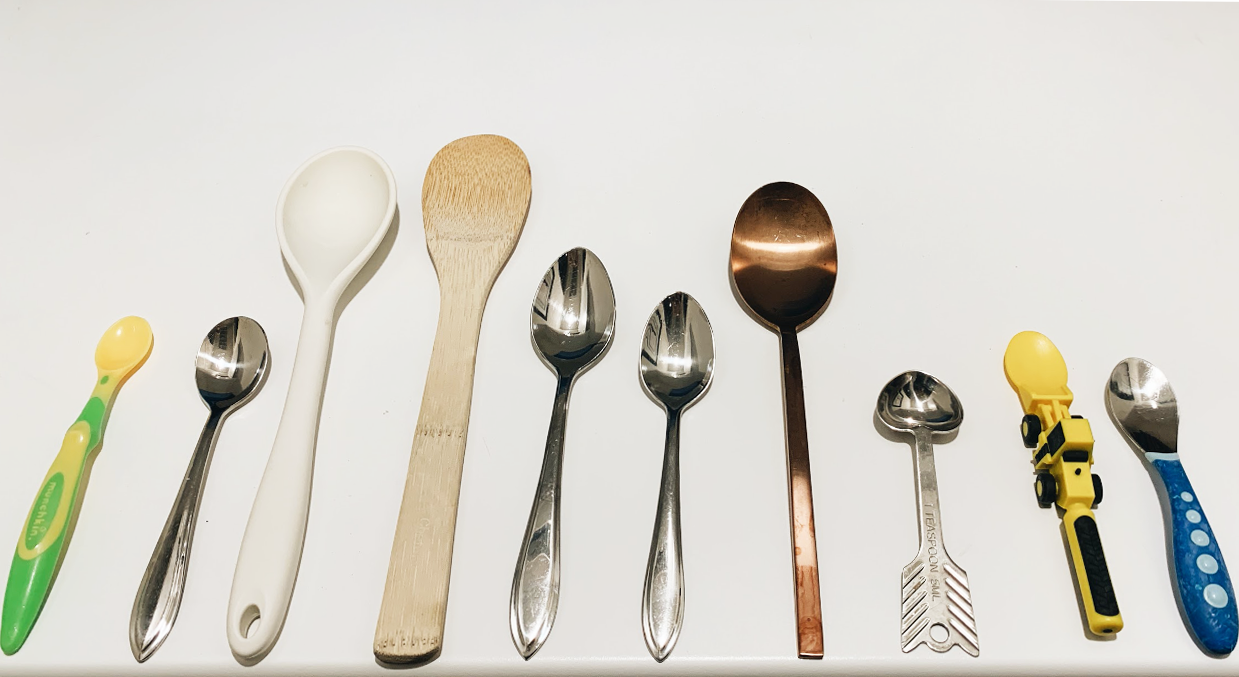 Some of the spoons are short and some are tall. The wooden one might be the tallest. The 3 shortest ones could all be the same size. More spoons are metal than plastic. 1 spoon has a truck on the handle. 3 spoons have the same handle but are different sizes.