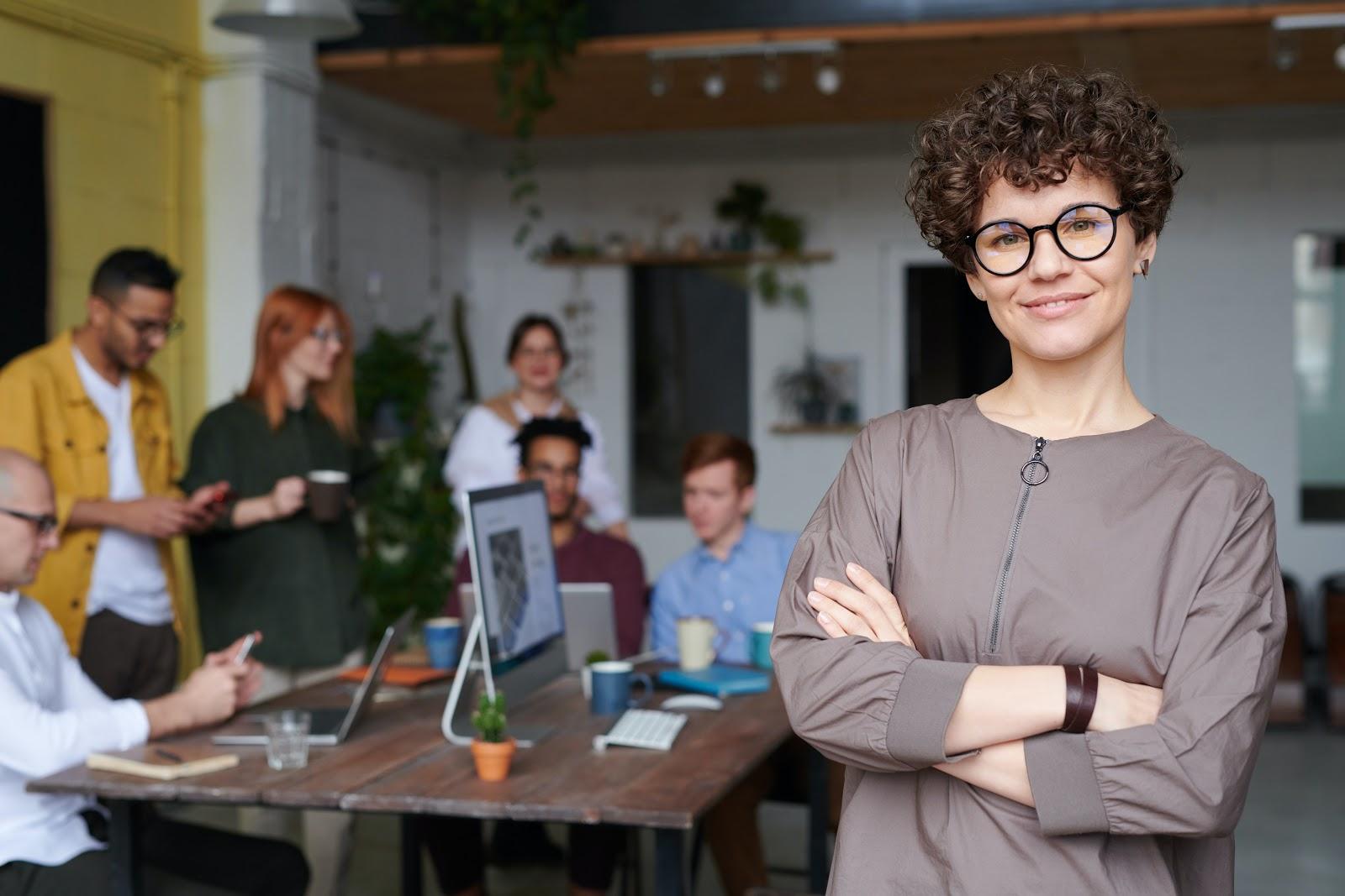 Uma mulher sorrindo na frente de várias outras pessoas conversando.