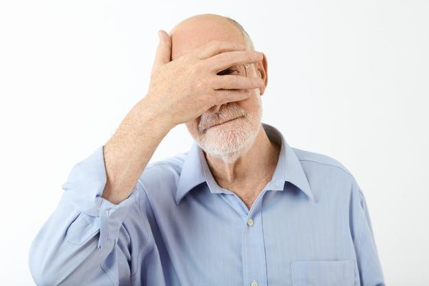 Portrait of elderly retired caucasian man in blue shirt holding hand on his face, covering eyes and peeking out through split fingers, feeling ashamed. human facial expressions and body language Free Photo