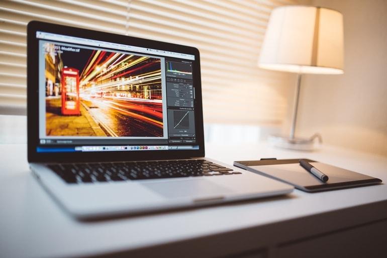 Laptop em um mesa com Lightroom aberto