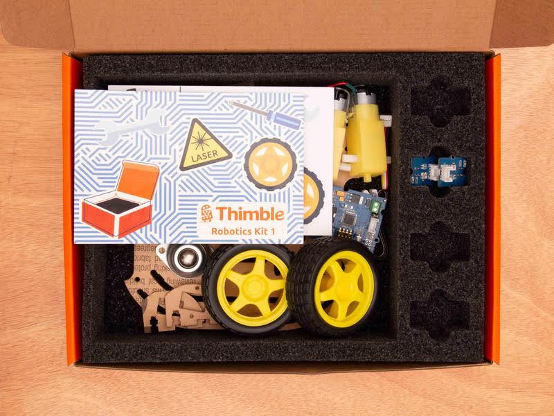 This is an image of the open Thimble wifi robot kit with the pieces and instruction card. This robotics kit for kids will teach you how to build a robot at home.