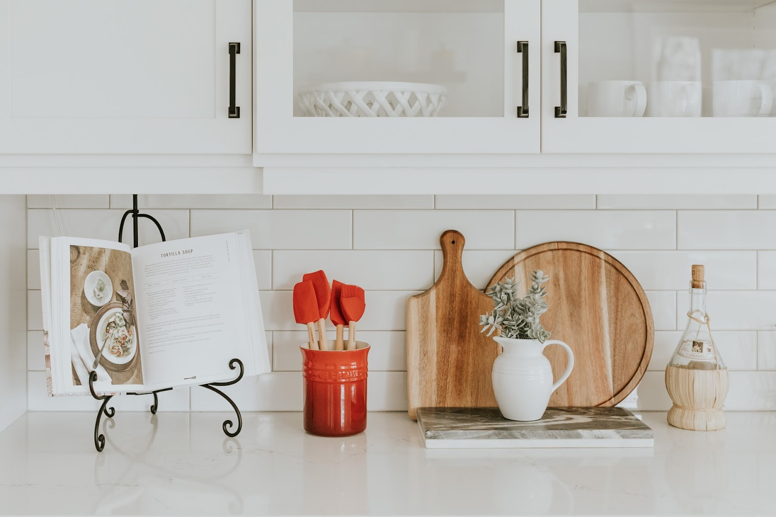 White cabinets, with a plant in a jar below, along with a bookstand and other elements.