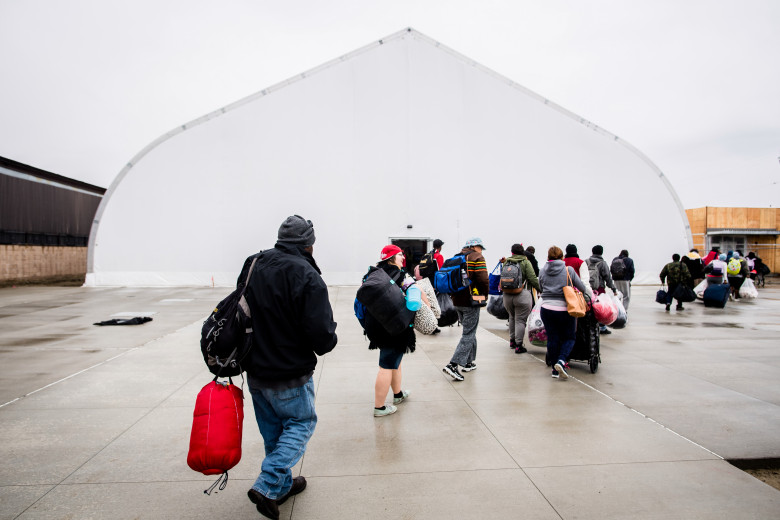 Tension fabric structure exterior receiving homeless shelter residents with who will have surge bed space inside