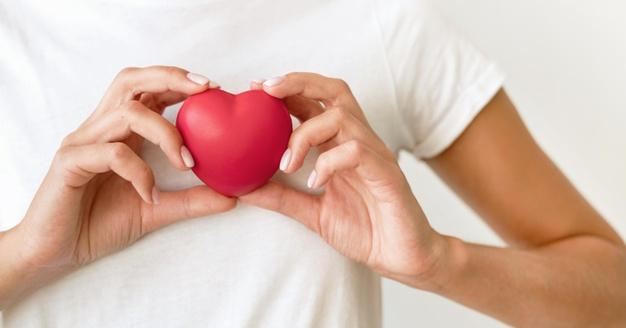 Front view of woman holding heart shape Free Photo