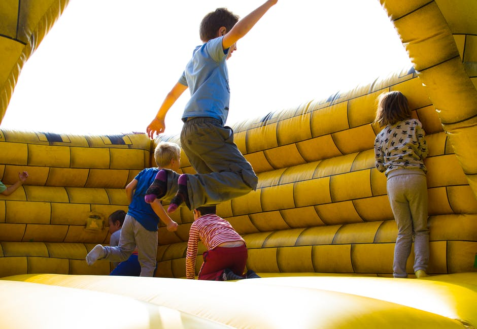 Kids Jumping in a Bouncy House at a Birthday Party