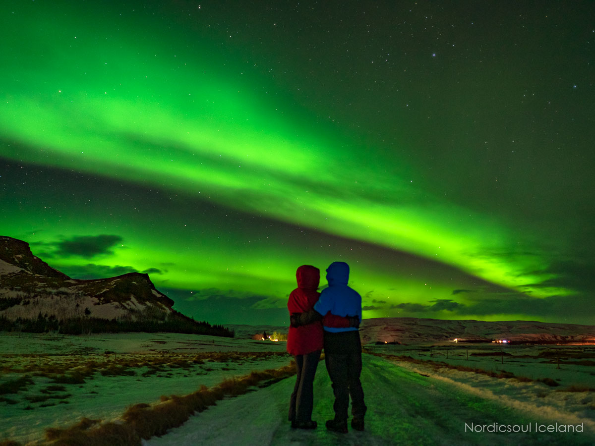 A couple standing under the Northern Lights on a country road in Iceland
