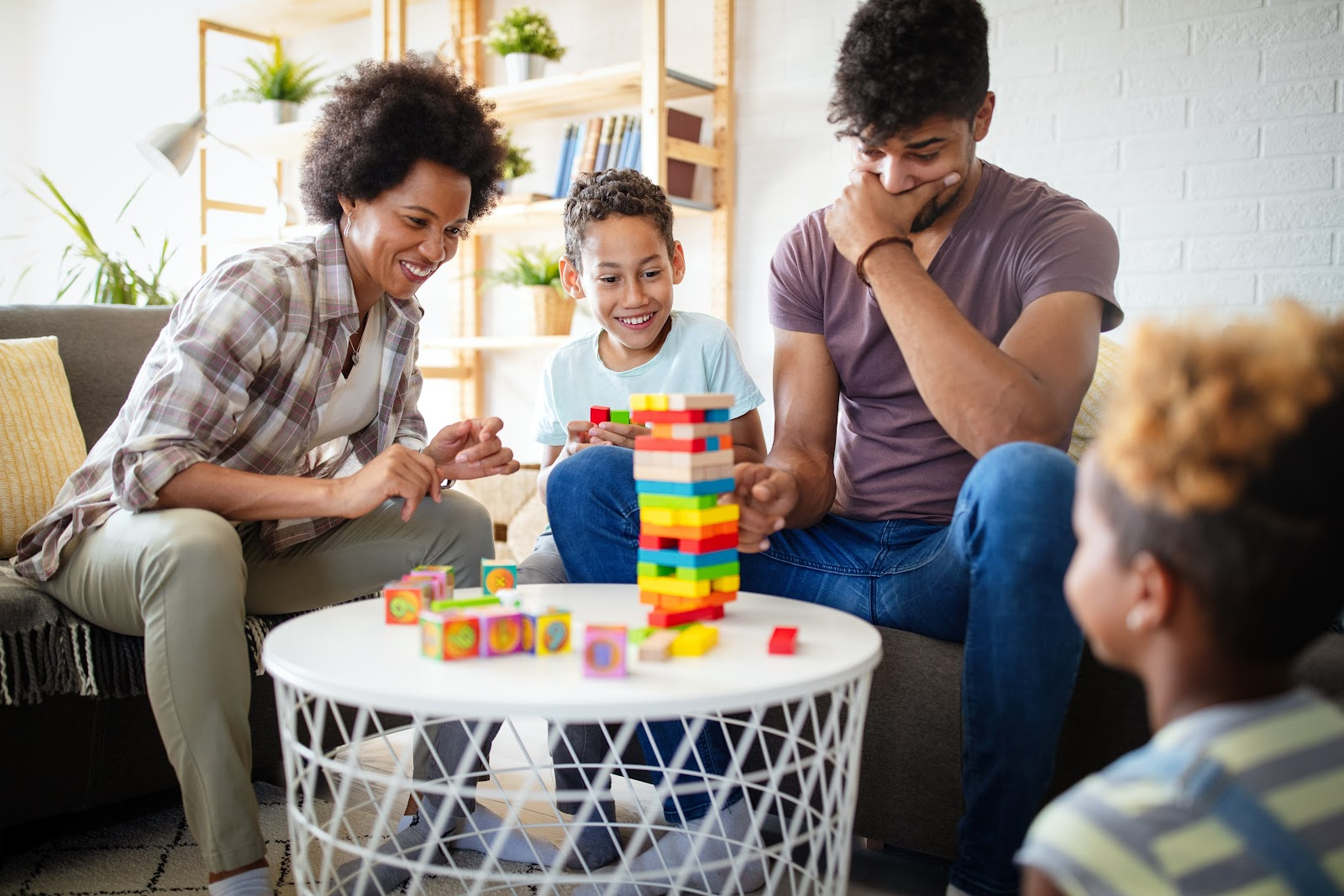 A family gathered around a coffee table playing Jenga.